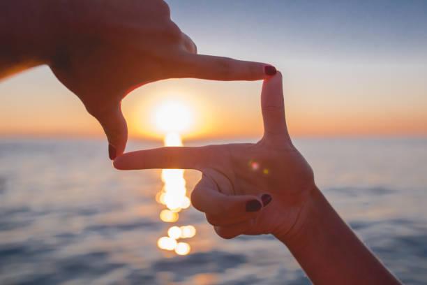 指フレームの女性の手は、背景上に逆光の夕日をキャプチャします。 ストックフォト