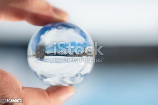 Finger holding a crystal or glass ball, winter landscape reflection, snow and trees with blue sky, copyspace