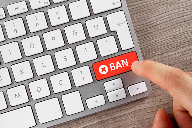 finger is pushing ban button on computer keyboard - disbarment stock pictures, royalty-free photos & images