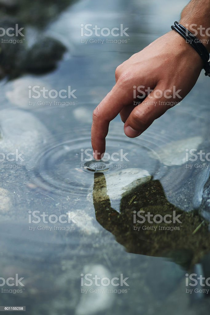 finger of man touching stream – Foto
