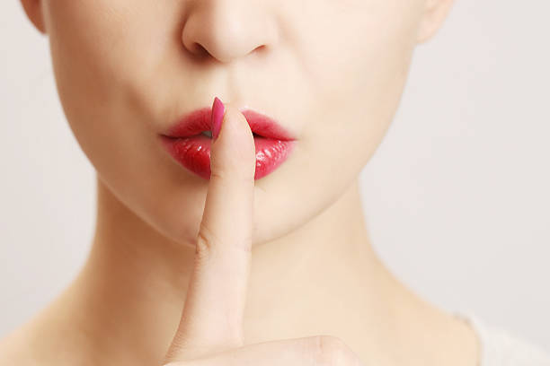 Finger on lips - silent gesture stock photo