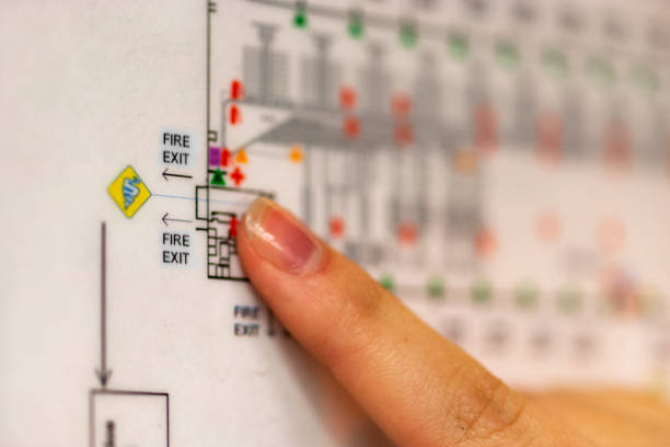 A finger pointing at an emergency exit on a building floor plan stock photo