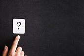 istock Finger pointing to the sign of question on the black background. Solution search concept. Empty place for a text. 843582822