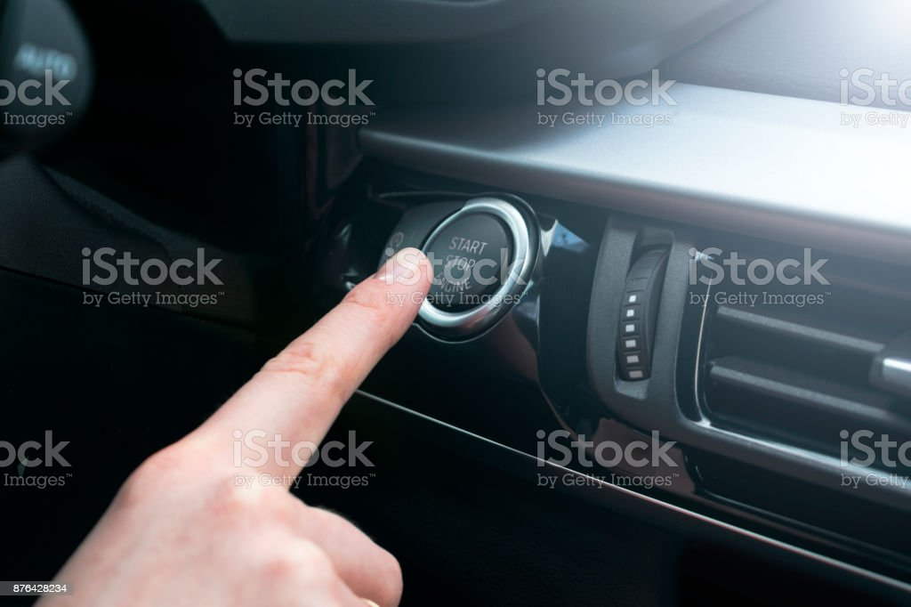 Finger press button functions car engine start and stop in motor vehicle for pre start checklist concept. Modern car interior details. Soft lighting stock photo