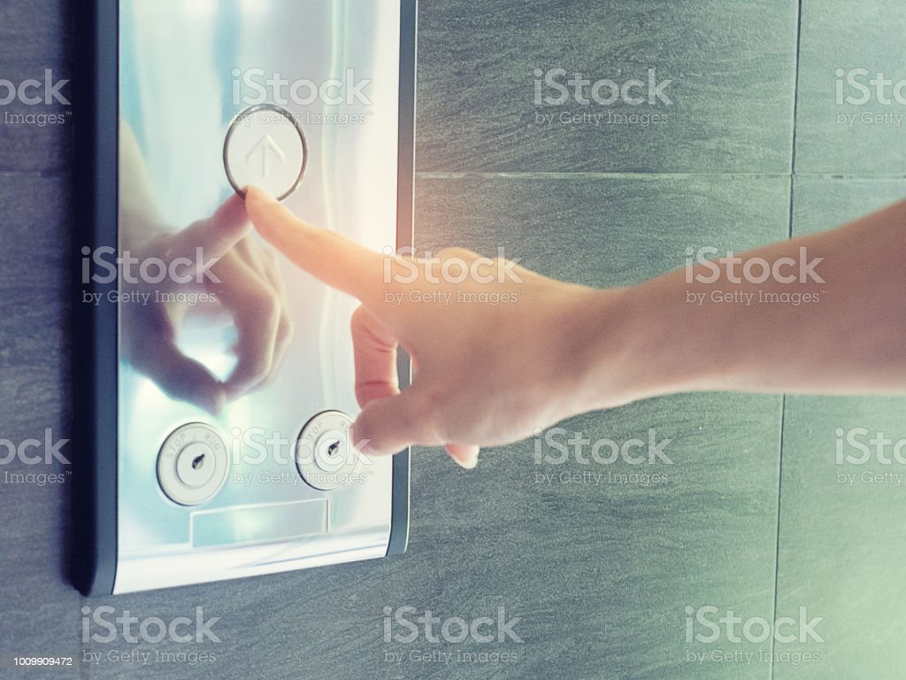 dedo aperta o botão do elevador, subindo e descendo button.woman pressionando o botão do elevador. dedo aperta o botão do elevador. - foto de acervo
