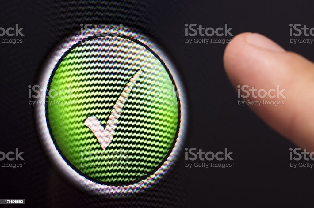 Finger pressing a green tick button on touchscreen royalty-free stock photo