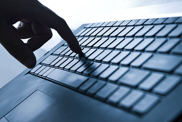 Finger pressing laptop keyboard stock photo