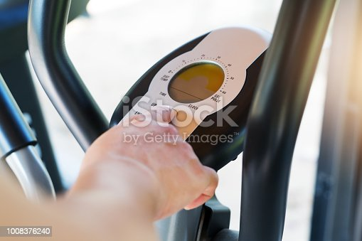 istock finger pressing on button of elliptical bike machine in fitness gym 1008376240