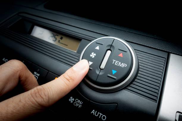 Dedo que presiona el interruptor del ventilador de un sistema de aire acondicionado del coche - foto de stock