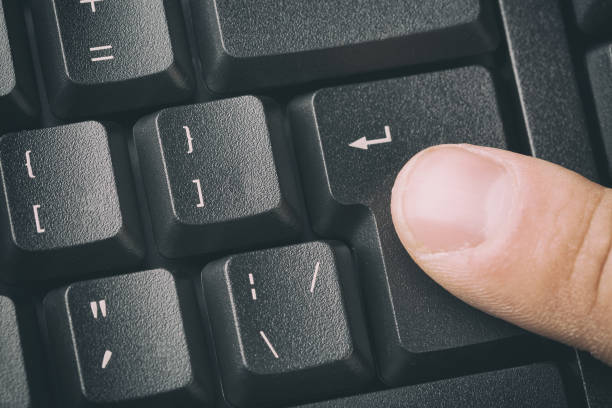 Finger pressing the ENTER button of keyboard. Close up and toned image. Finger pressing the ENTER button of keyboard. Close up and toned image enter key stock pictures, royalty-free photos & images