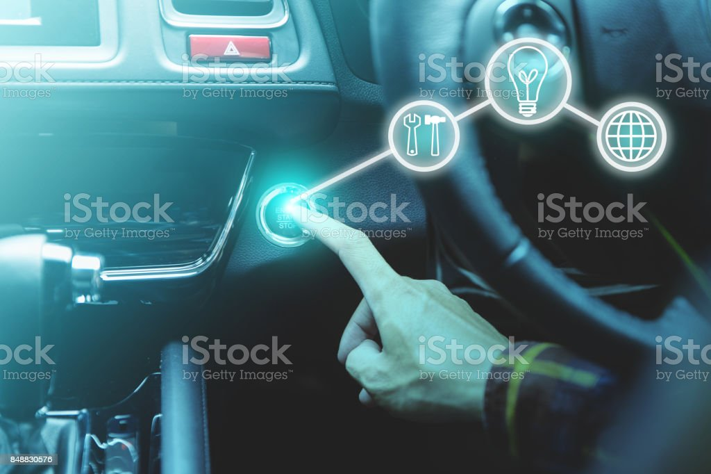 finger pressing the start/stop engine button on car with business icons for startup concept. stock photo
