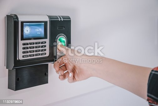 Close up shot of female hand touching fingerprint recognition scanner and access control for enter security system open door on wall in a factory warehouse building