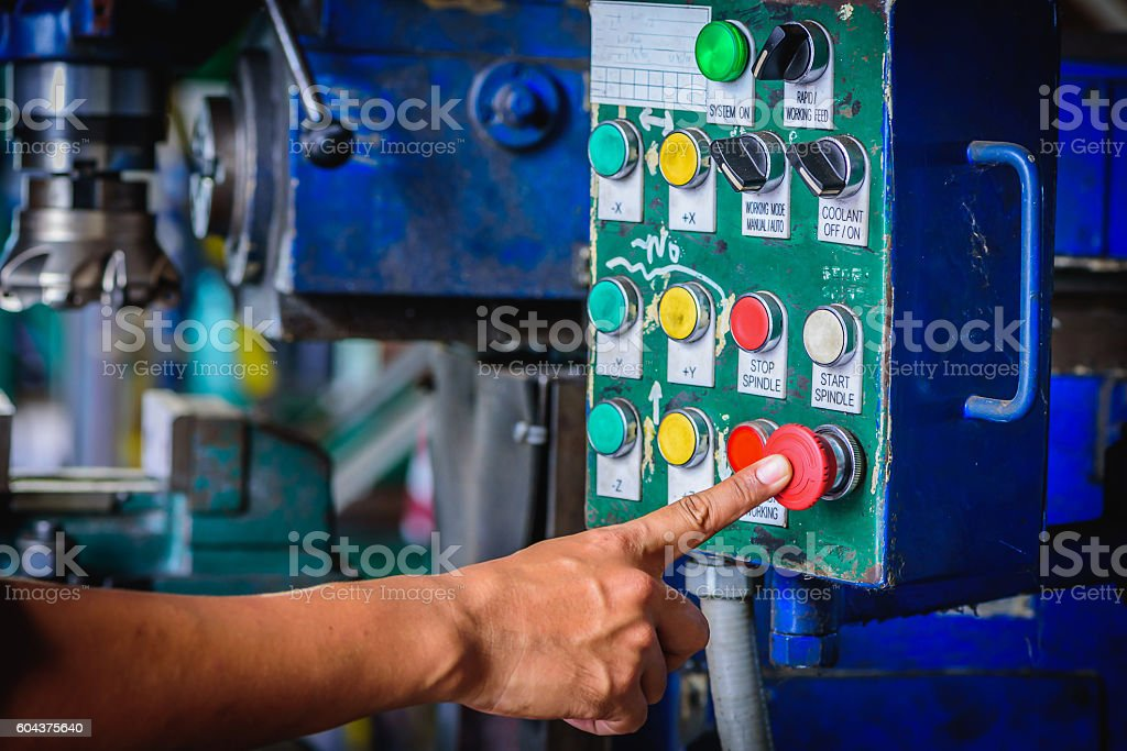 Finger push on red emergency stop switch milling machine stock photo