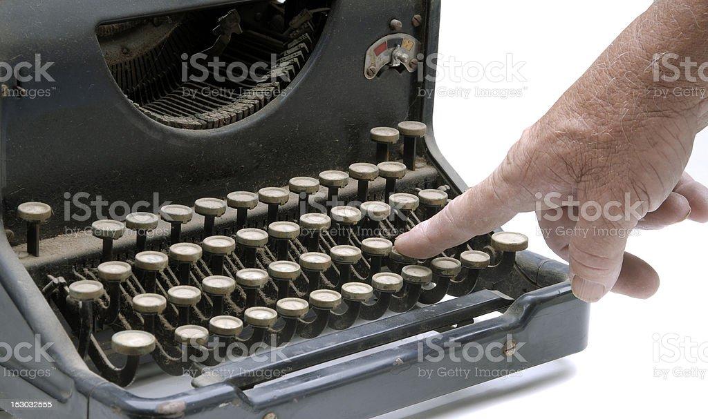 Finger pushing a key on vintage typewriter royalty-free stock photo