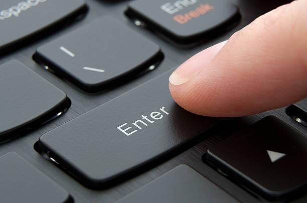 Finger pushing enter black button Finger pushing enter button on black computer keyboard; Macro photo enter key stock pictures, royalty-free photos & images