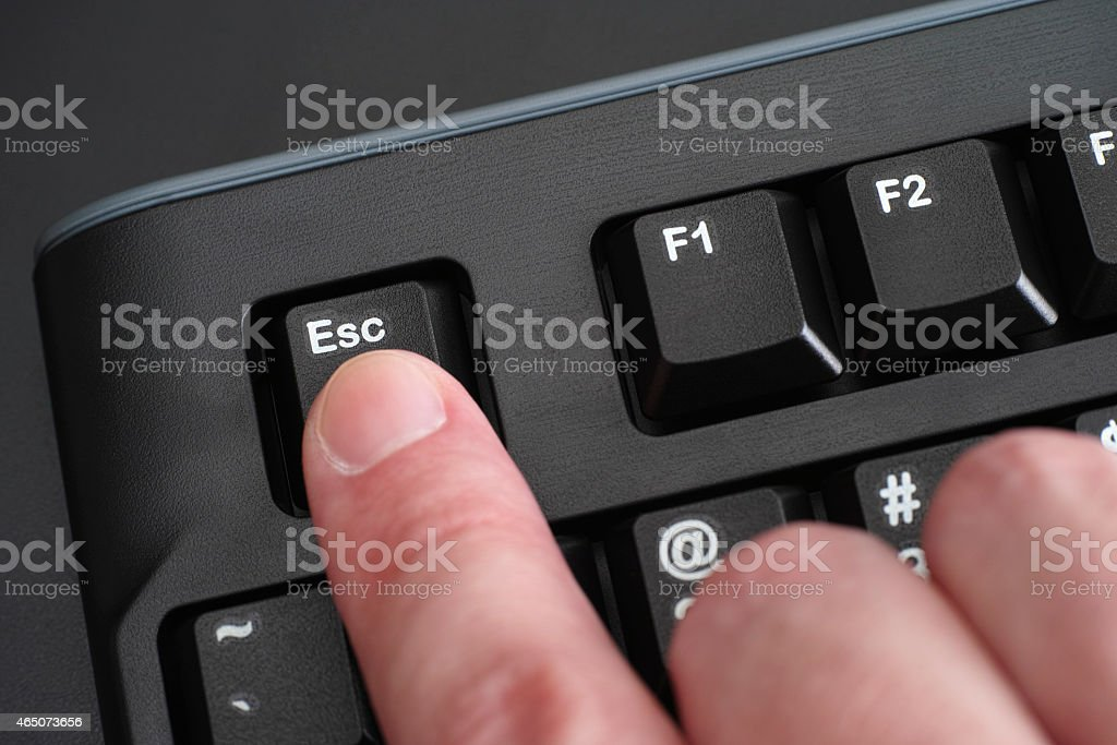 Finger pushing Esc key on black keyboard stock photo