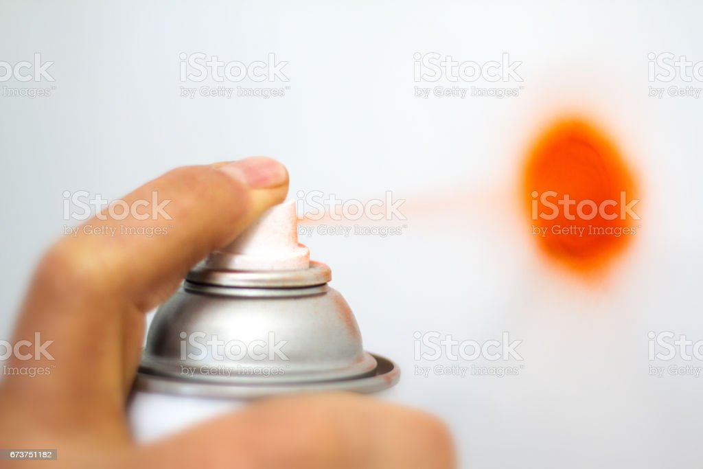 Finger Spraying Aerosol Orange Paint, Close-Up, White Background royalty-free stock photo