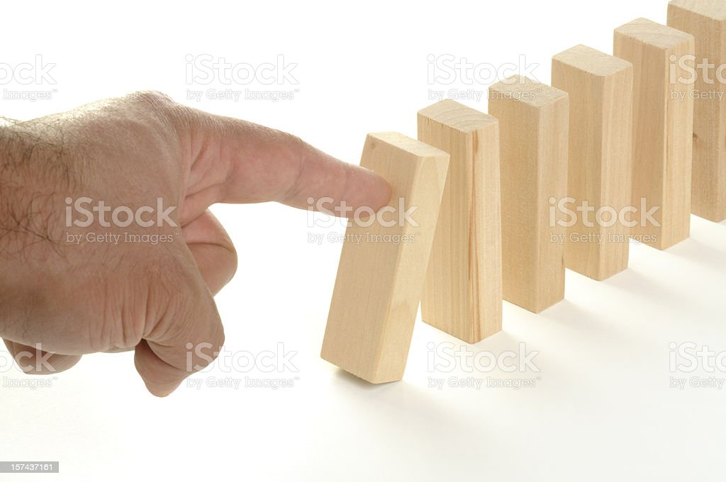 A finger tapping a block of wood on a white background stock photo