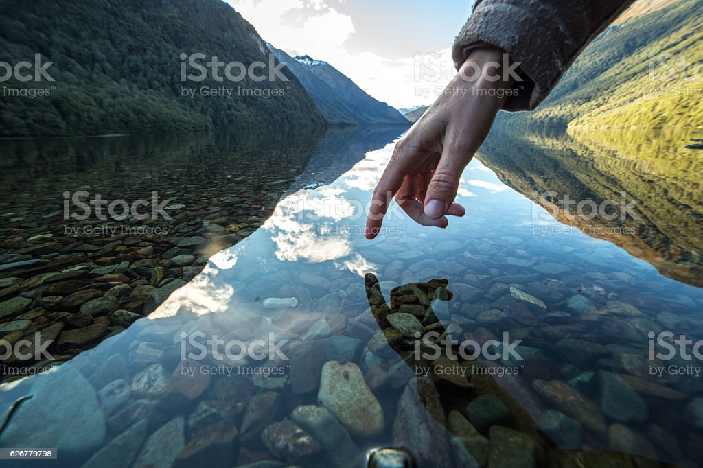 Finger touches surface of mountain lake, New Zealand stock photo