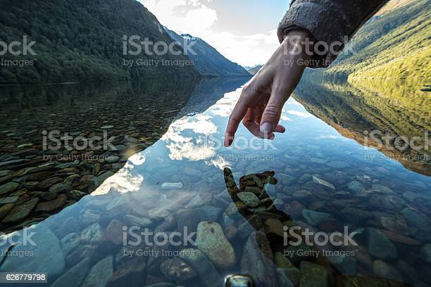 Photo of Finger touches surface of mountain lake, New Zealand