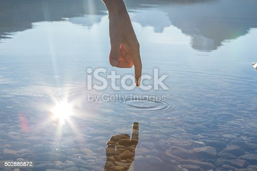 Finger touches surface of mountain lake. The sun and the landscape is reflecting on the water.
