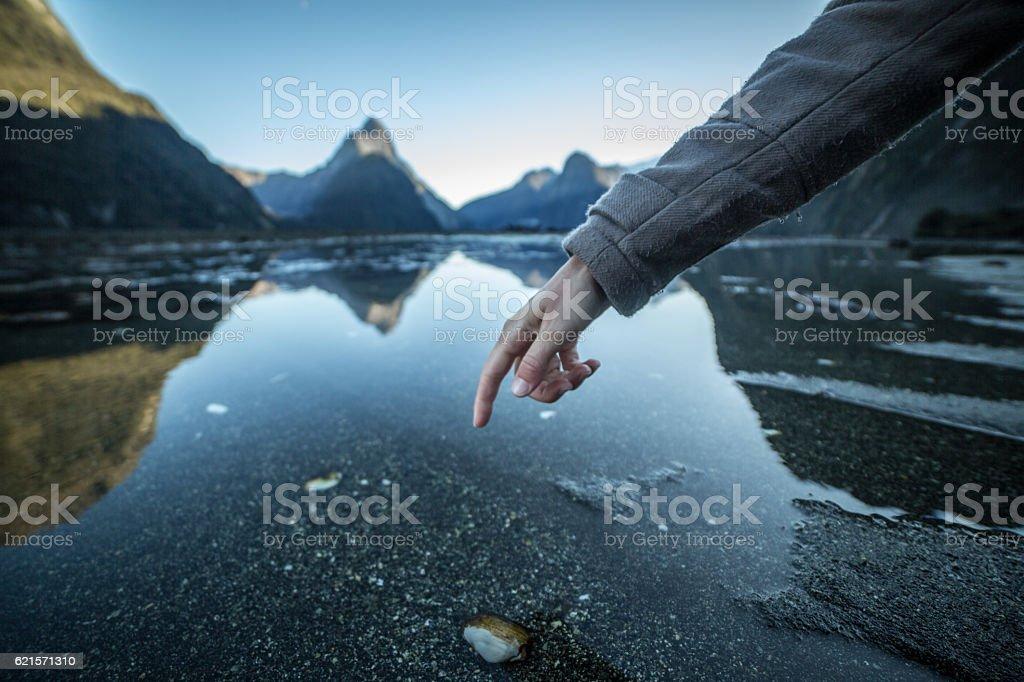 Doigt touche la surface d'un lac de montagne photo libre de droits