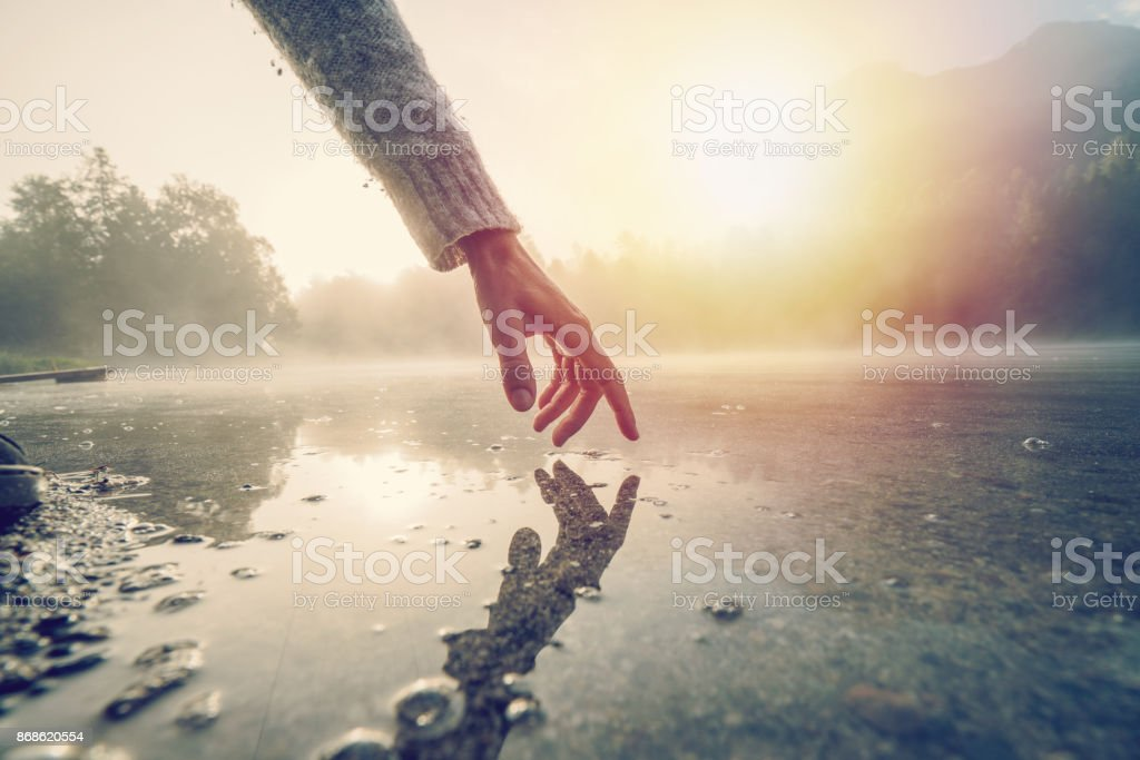 Finger touches surface of mountain lake, Switzerland stock photo