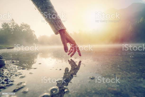 Finger Touches Surface Of Mountain Lake Switzerland Stock Photo - Download Image Now