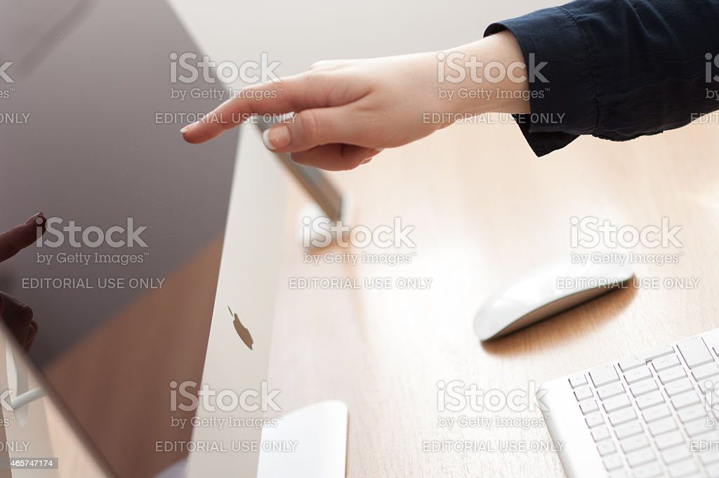 Finger touching Apple iMac computer screen. stock photo
