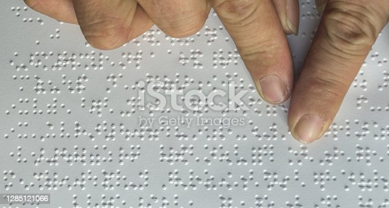 Braille book for low vision/ blind person reading Braille sign by finger touching embossed texture paper for World sight day and World Braille day awareness concept