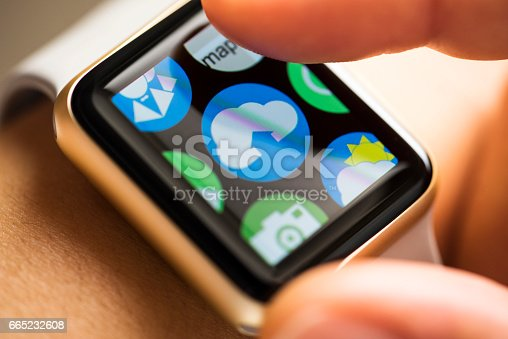 istock Finger touching cloud computing app icon on smart watch screen 665232608