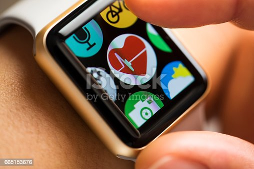 Close up shot of woman wrist wearing smart watch. Finger touching health track app icon on touchscreen.