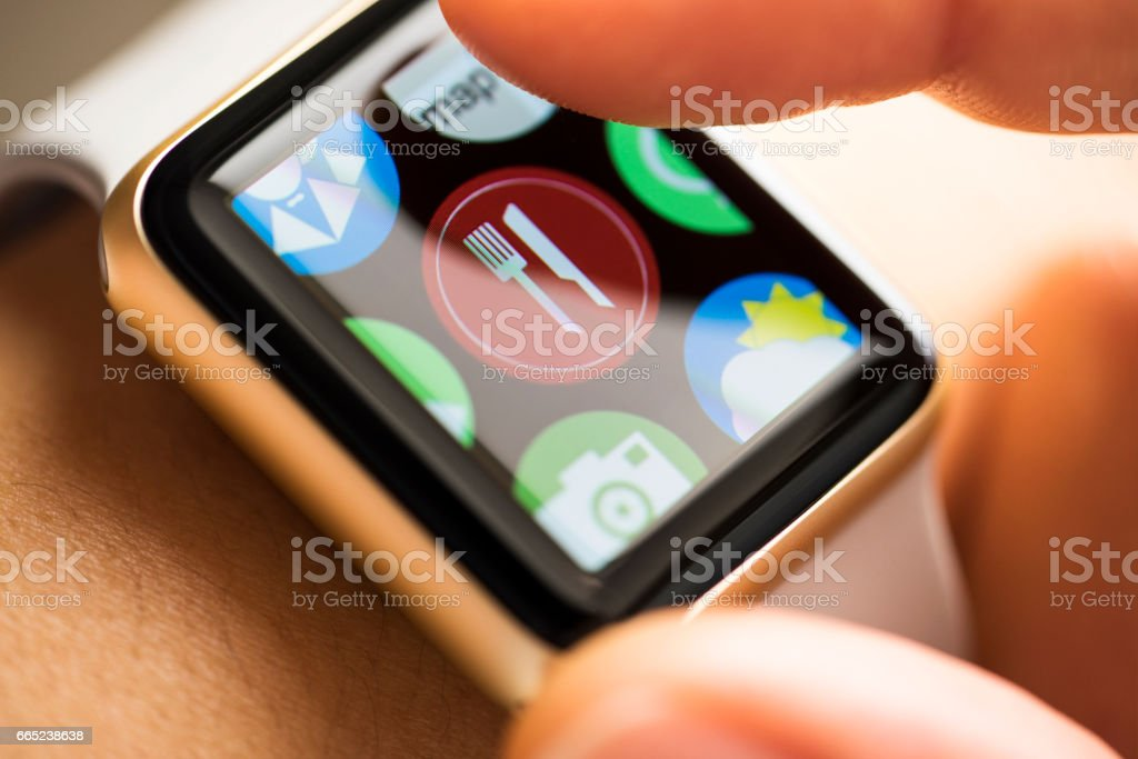 Finger touching online food oredering app icon on smart watch screen stock photo
