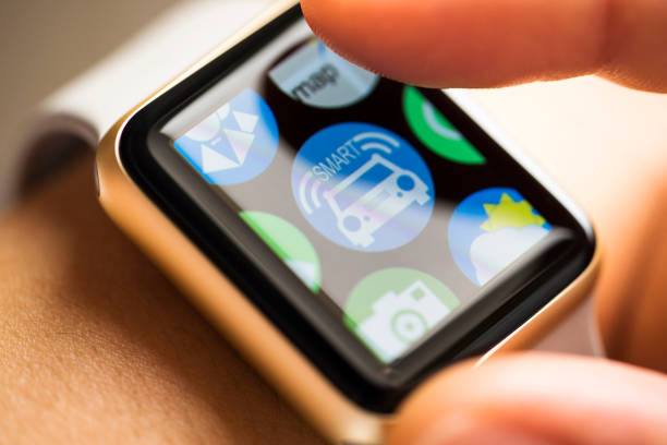 Finger touching smart car app icon on smart watch screen stock photo