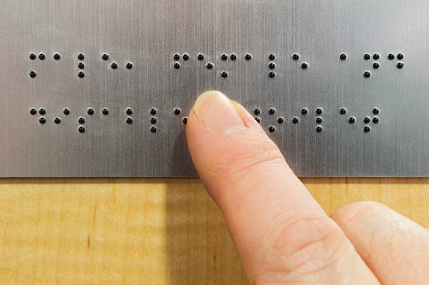 Finger tracing Braille letters over a gray background stock photo