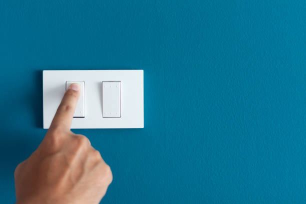 un doigt en tournant le commutateur d'éclairage sur rugueux sur un mur foncé bleu. - commutateur photos et images de collection