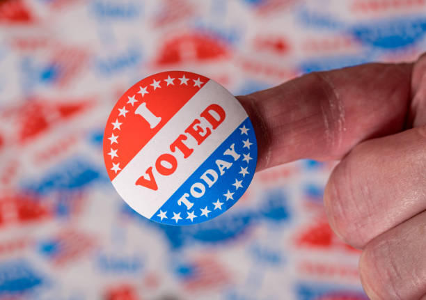 Finger with I Voted Today sticker in front of background created from many election voting badges stock photo