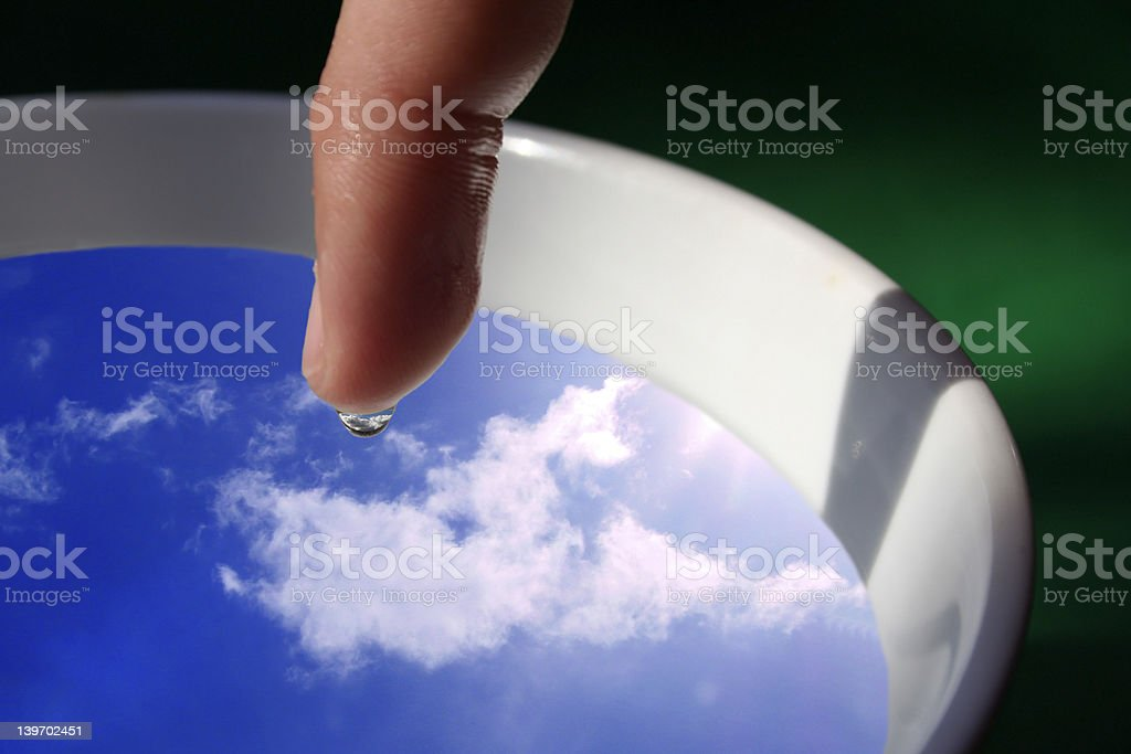 finger with water droplet in focus and sky inside it royalty-free stock photo
