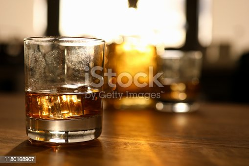 Fingerprint on glass with whiskey stands wooden oak table background. Alcohol addiction concept