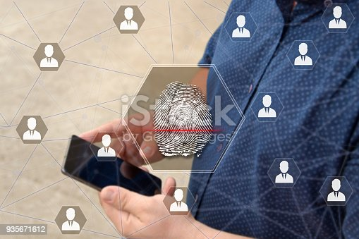 896596886 istock photo Fingerprint scanning on the touch screen with a blur background of the businessman with the phone.The concept of Secure access through fingerprint scanning to the network 935671612