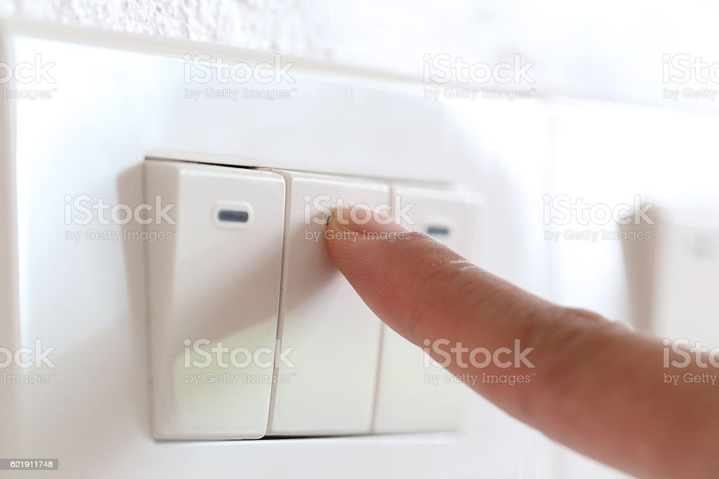 fingers are off light switch in the house. stock photo