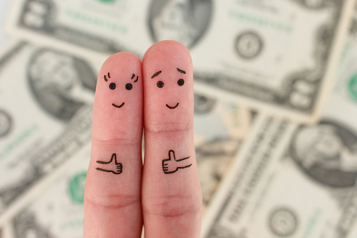 istock Fingers art of a Happy couple. Man and woman show sign of class on background of money. 807236122