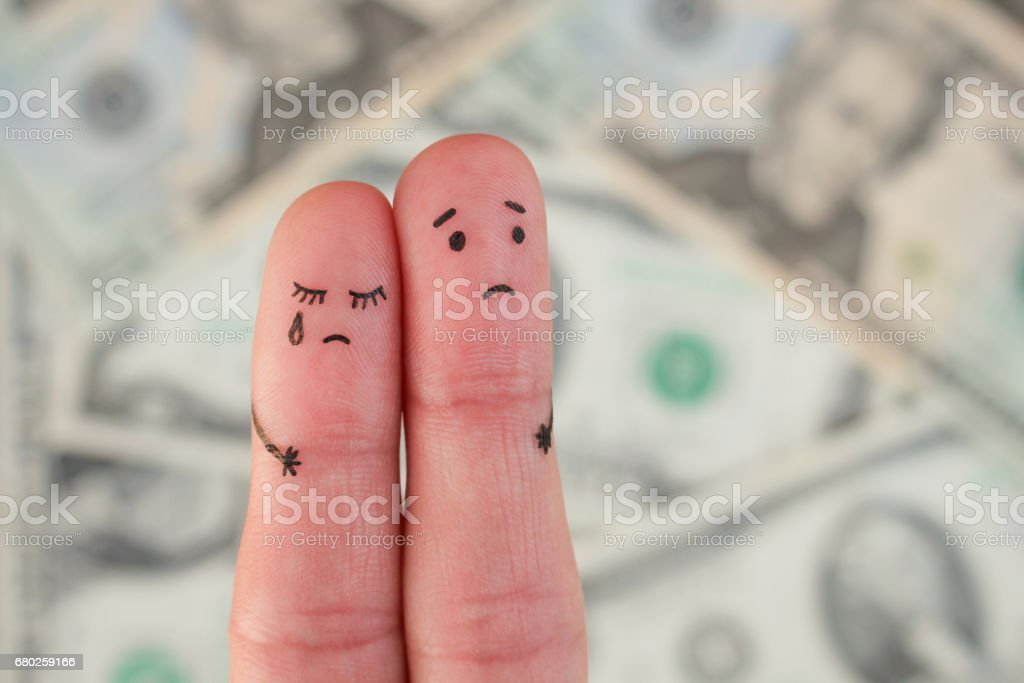 Fingers art of displeased couple on background of money. Concept of poor people. stock photo