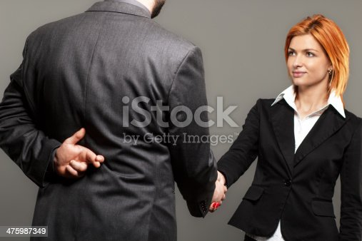 Business partners shaking hands with one of them holding fingers crossed behind back.