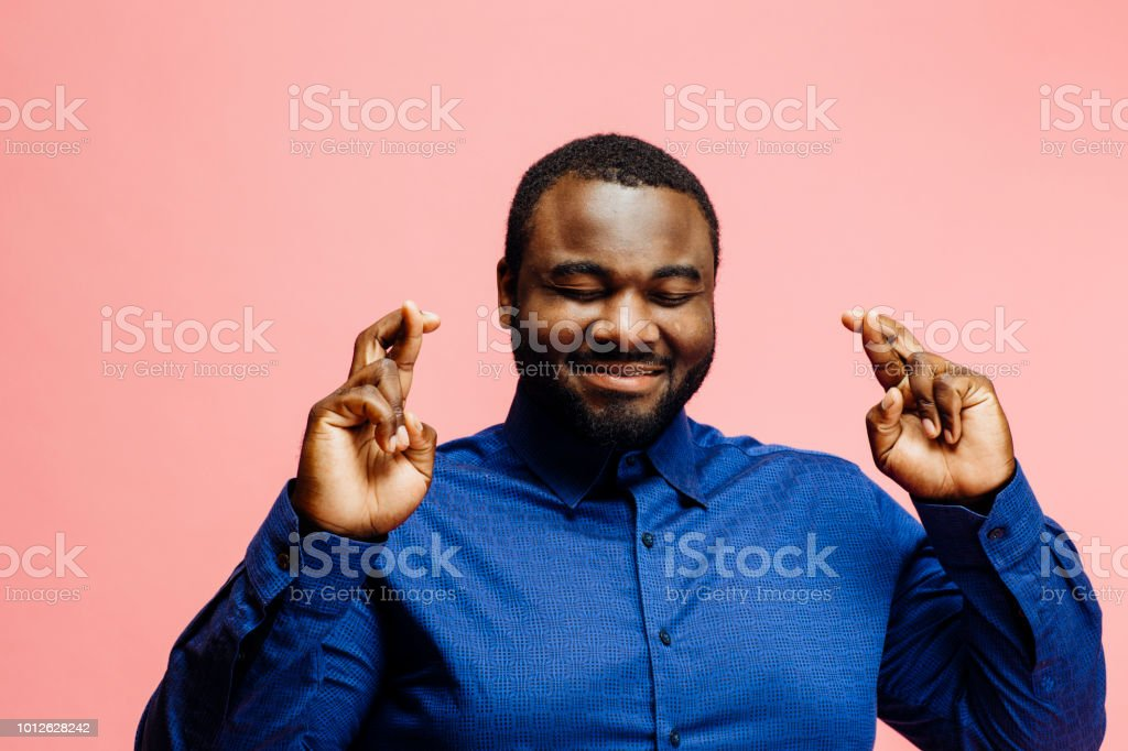 Wishing for good luck, portrait of a smiling man in blue shirt with...