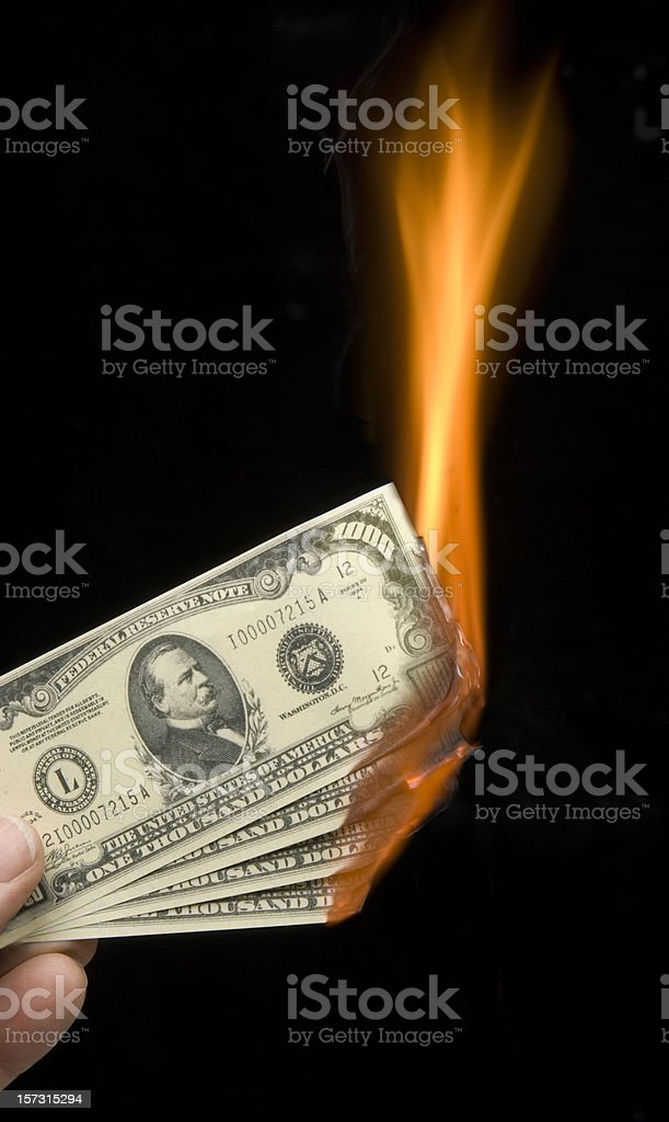 Fingers holding burning thousand dollar bills-money to burn stock photo