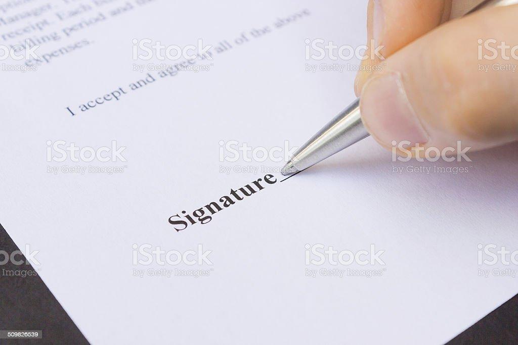 Fingers holding pen writing signature stock photo