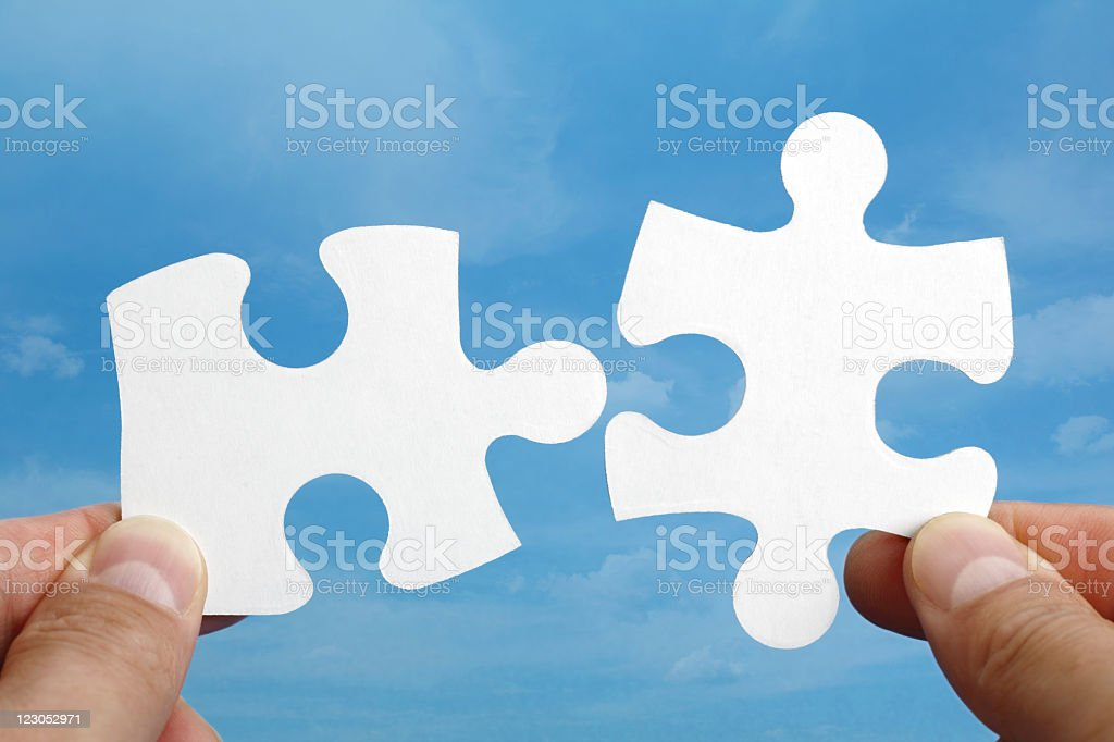 Fingers holding two pieces of a puzzle that fit together royalty-free stock photo