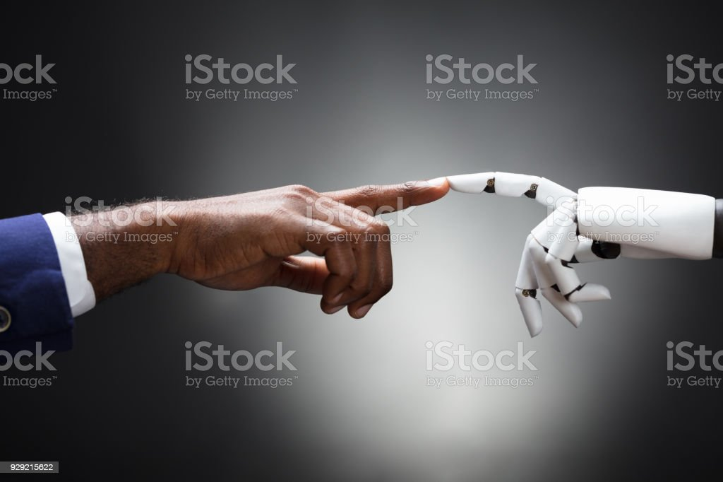 Fingers Of Robot And Man Touching stock photo