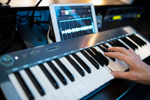 Fingers of young contemporary pianist pressing keys of piano keyboard Fingers of young contemporary pianist pressing keys of piano keyboard while recording music by workplace in studio synthesizer stock pictures, royalty-free photos & images